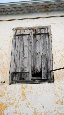 Old window shutters on a yellow building