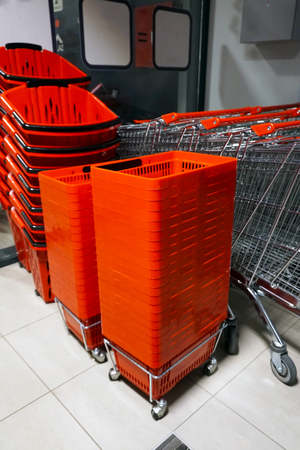 Rows of aligned shopping carts and red baskets. Banque d'images - 96169424