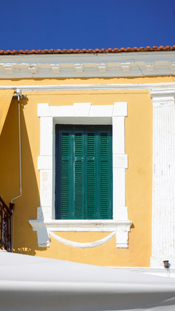 Green window shutters on a yellow building  Banque d'images
