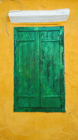 Green window shutters on a yellow building  Stock Photo