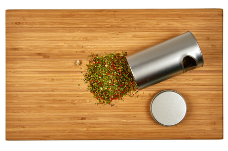 loose leaf: Colorful mate tea infused with herbs spilled from tin can on wooden background