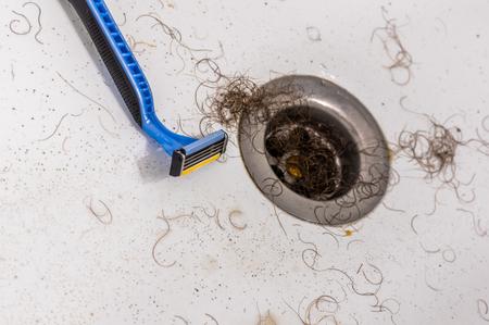 Pubic hair clogged shower drain Stock Photo
