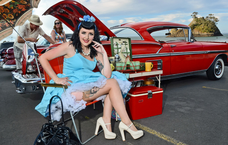 Vintage styled young woman and classic car