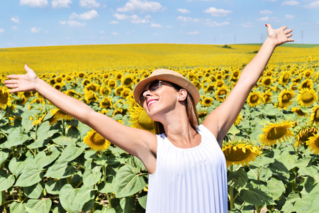 spreaded: Young woman wearing straw hat and sunglasess in the middle of a sunflower farm