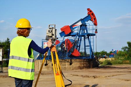 A female land surveyor engineer at work on an European petroleum well