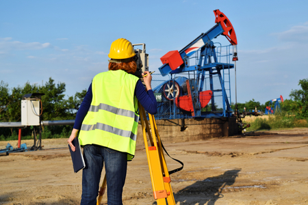 A female land surveyor engineer at work on an European petroleum well