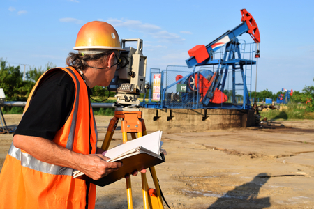 A male land surveyor engineer at work on an European petroleum well Stock Photo