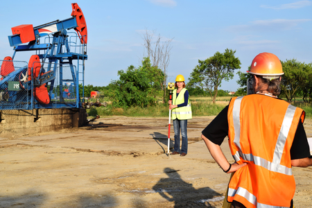 oil well pumper: Two land surveyor engineers at work on an European oil well. Petroleum pumpjack  in background