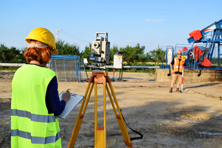 Two land surveyor engineers at work on an European oil well. Petroleum pumpjack  in background