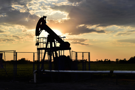 Silhouette of a grasshopper crude oil pump during sunset time