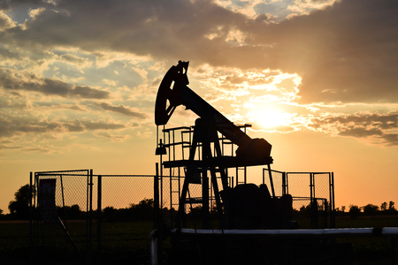 oil well pumper: Silhouette of a grasshopper crude oil pump during sunset time