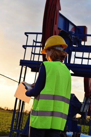 A female petroleum technician does regular check on an European oil well during twilight