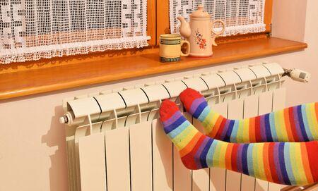 Una mujer con calcetines a rayas disfrutando del invierno en una habitación cálida y acogedora