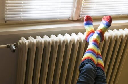 A woman in striped socks enjoying winter in a cozy, warm room (low light)