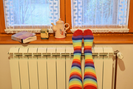 A woman in striped socks enjoying winter in a cozy, warm room