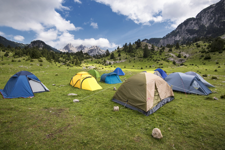 A few pitched tents in the valley beneath the mountain on a sunny day Stock Photo