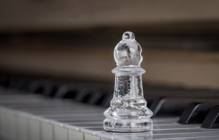 Glass chess bishop on the old piano Stock Photo