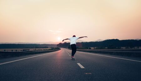 Man with arms outstretched riding a skateboard on the motorway road toward the setting sun in the background. The background is slightly blurred, focus on a skateboarder in the foreground.