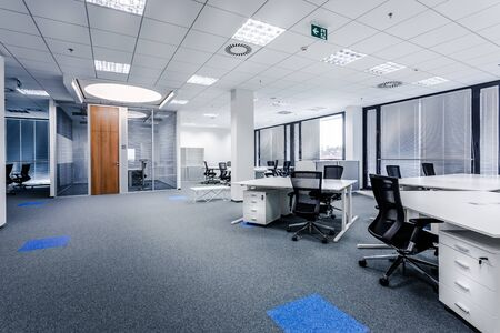 Part of ordinary office room decorated in modern style with meeting room,large windows with blinds,carpeting,ventilation,escape signs,white furniture (tables, shelves, drawers) and dark office chairs.