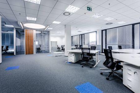 Teil eines gewöhnlichen Büroraums im modernen Stil mit Besprechungsraum, großen Fenstern mit Jalousien, Teppichboden, Belüftung, Rettungszeichen, weißen Möbeln (Tische, Regale, Schubladen) und dunklen Bürostühlen.