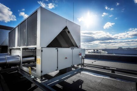 A huge air conditioning unit on the roof of the building. In the background of blue sky with shining sun. Focus is at the front of the air conditioner, the other parts of image slightly blurred.