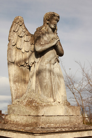 gravesite: Figure of a praying angel on a blue sky