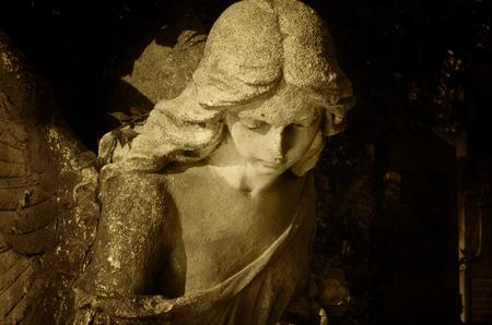 ali angelo: scultura di un angelo d'oro con sfondo scuro Archivio Fotografico