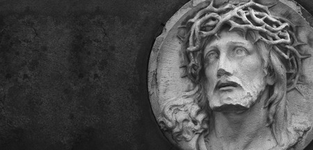 Jesus Christ statue against a background of gray stone with space for text Archivio Fotografico