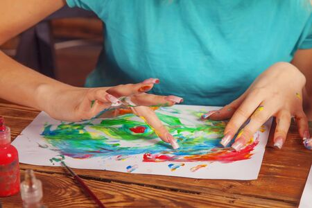 Art and creativity concept. Portrait of young beautiful woman painting with fingers.   Archivio Fotografico
