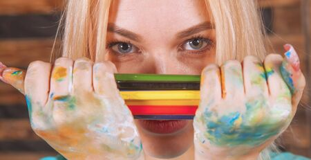 Humorous photo of great artist. Portrait of beautiful young woman painting with colored pencils. Archivio Fotografico