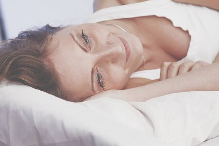 Portrait of happy pretty positive young woman in bed smiling after wake up. Horizontal image. Archivio Fotografico