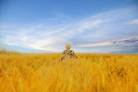 Beautiful blond woman enjoying the life, freedom and nature outdoors in the summer field of wheat Archivio Fotografico