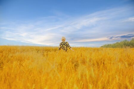 Young beautiful blonde woman standing on a wheat field against dramatic sky background.