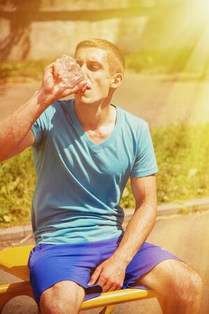 Sport, health and lifestyle concept. Young athletic man after training drinking water from bottle. Vertical image.