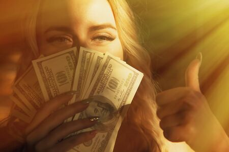Portrait of young beautiful woman with US Dollar bills making Ok gesture as if she want to say: Money really can buy You happiness.