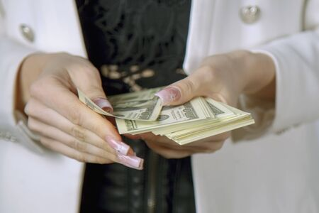 Close up business woman recounts US Dollar bills. Earnings, profits, accounting concept. Archivio Fotografico