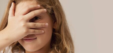 Young beautiful child girl peeking behind her hand and finger as a symbol of trickery and deceit.