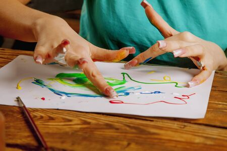 Art therapie and creativity concept. Beautiful young woman painting with finger