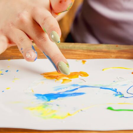 Art as psychological therapy for mental health. Young beautiful woman painting with fingers.  Selective focus.