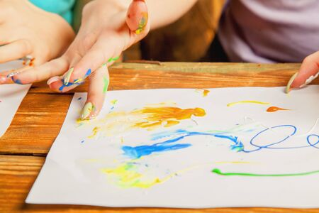 Art as psychological therapy for mental health. Young beautiful woman painting with fingers.  Inspiration and creativity concept. Selective focus on fingers.