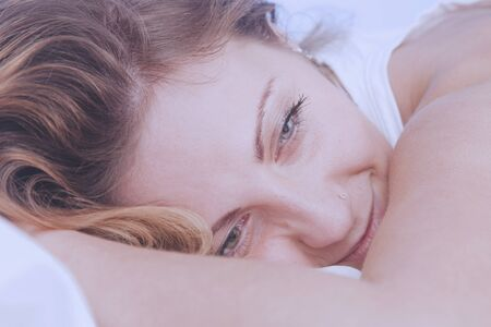 Sleep and rest after hard and successful work. Young beautiful woman falls asleep in bed with smile on her lips. Archivio Fotografico