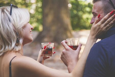 Couple in love drinking brandy outdoors in park.