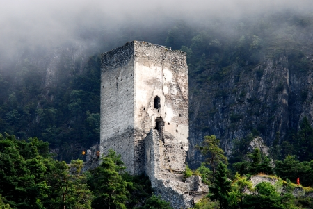ruin in the mountains surrounded by trees and haze