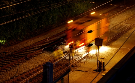 man working at rails at night photo