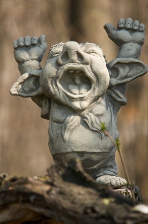 clay figure with hands up standing on a trunk