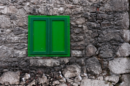 stony house wall with a closed green window photo