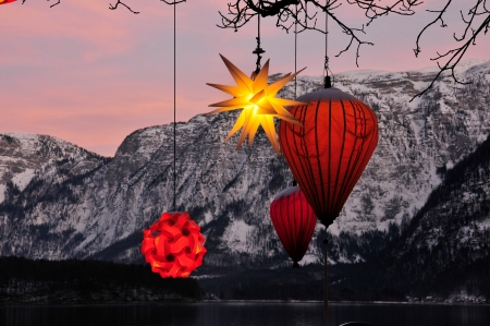 glowing Chinese lanterns hanging down from a tree with mountains in the background photo