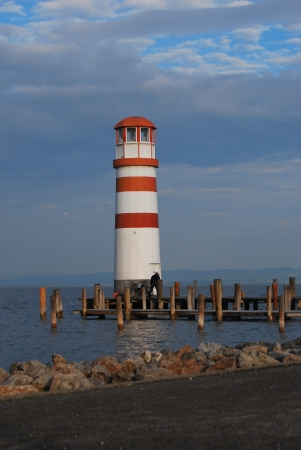 red and white striped lighthouse with a view over the lake Stock Photo