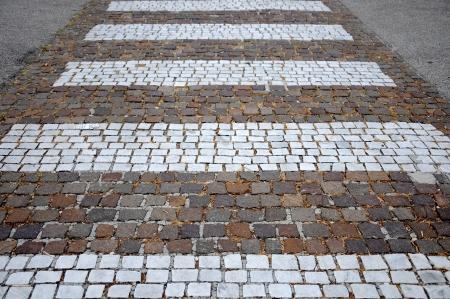 white stripes across the street_Pedestrian crossing made of cobblestones Stock Photo