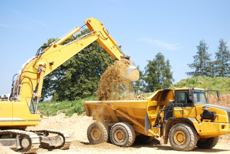 a digger loading a truck with earth